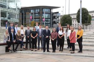 Pictured are last year's graduate intake to KPMG in Northern Ireland with partner John Poole, centre, outside the firm's Soloist Building in Belfast