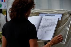 A woman looks at the condolences book in tribute to the victims of Paris attacks outside the French embassy in Singapore on November 16, 2015. Islamic State jihadists claimed a series of coordinated attacks by gunmen and suicide bombers in Paris on November 13 that killed at least 129 people in scenes of carnage at a concert hall, restaurants and the national stadium. AFP PHOTO / ROSLAN RAHMANROSLAN RAHMAN/AFP/Getty Images