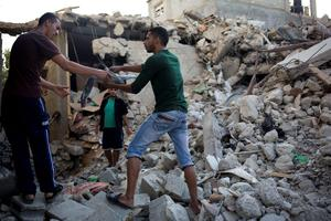 Palestinians pass parts of a missile which destroyed the house of the Najam family in the Jebaliya refugee camp, Gaza Strip, Monday Aug, 4, 2014. Seven Najam family members were killed in an Israeli missile strike on their home Sunday night and many more were wounded, a health ministry official said. (AP Photo/Dusan Vranic)