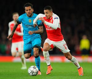 LONDON, ENGLAND - FEBRUARY 23:  Alexis Sanchez of Arsenal takes on Dani Alves of Barcelona during the UEFA Champions League round of 16 first leg match between Arsenal and Barcelona on February 23, 2016 in London, United Kingdom.  (Photo by Paul Gilham/Getty Images)