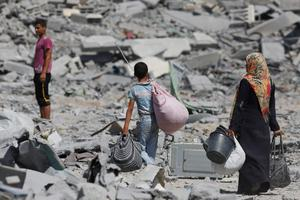 Palestinians carry their belongings after salvaging them from their destroyed houses in the heavily bombed town of Beit Hanoun, Gaza Strip, close to the Israeli border, Friday, Aug. 1, 2014.  (AP Photo/Lefteris Pitarakis)