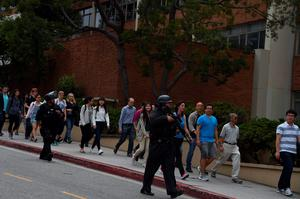 People are escorted by security personnel at the University of California Los Angeles campus after two people were confirmed dead following a shooting at the facility, June 1, 2016 in Los Angeles, California. Dozens of police cars and tactical response teams as well as federal agents rushed to the site as helicopters hovered overhead.  Some 43,000 students are enrolled at the massive UCLA campus, according to its website.   / AFP PHOTO / Robyn BECKROBYN BECK/AFP/Getty Images