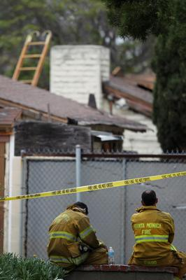 SANTA MONICA, CA - JUNE 07:  Firefighters sit near a burned house they extinguished before finding two bodies inside after multiple shootings were reported at various locations including Santa Monica College June 7, 2013 in Santa Monica, California. According to reports, at least six people have died in the shootings.  (Photo by David McNew/Getty Images)