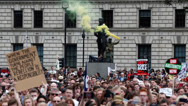 A demonstrator stands on the statue of former South African prime minister Jan Smuts in Parliament Square holding a smoke flare as thousands of demonstrators gather to listen to speeches during a protest against the British government's spending cuts and austerity measures in London on June 20, 2015. The national demonstration against austerity was organised by People's Assembly against government spending cuts.   AFP PHOTO / JUSTIN TALLISJUSTIN TALLIS/AFP/Getty Images