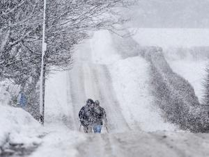 Walkers trudge through the Snow on the Outskirts of Armoy in Northern Ireland. Photo Colm Lenaghan/Pacemaker Press