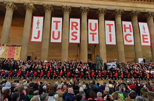 Youth team players from the Liverpool and Everton football clubs prepare to lay 96 single red roses, representing the 96 victims of the 1989 Hillsborough disaster, on the steps of St George's Hall in Liverpool, north west England on April 27, 2016, in remembrance of the Liverpool fans who died in the Hillsborough football stadium disaster. AFP/Getty Images
