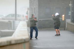 "People take selfies in waves and high wind at Lahinch in County Clare on the West Coast of Ireland as Hurricane Ophelia hits the UK and Ireland with gusts of up to 80mph. PRESS ASSOCIATION Photo. Picture date: Monday October 16, 2017. The tropical storm has made its way across the Atlantic and Ophelia's remnants reached home shores on Monday, resulting in ""exceptional"" weather - exactly 30 years after the Great Storm of 1987 killed 18 people. See PA story WEATHER Ophelia. Photo credit should read: Niall Carson/PA Wire"
