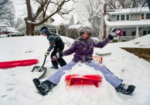 Nine-year-old Katie Swayne, right, throws snow into the air as her brother Bradley, 6, shovels a path in front of their house while the snow continues to fall in Winston-Salem, N.C., Wednesday, Feb. 12, 2014. (AP Photo/Winston-Salem Journal, Lauren Carroll)
