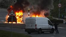 OMINOUS: A man tries to hijack a van in Newtownabbey last night as two cars are on fire nearby