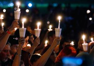 Attendees raise their candles at a candlelight vigil for the victims of the shooting at Marjory Stoneman Douglas High School, Thursday, Feb. 15, 2018, in Parkland, Fla. The teenager accused of using a semi-automatic rifle to kill more than a dozen people and injuring others at a Florida high school confessed to carrying out one of the nation's deadliest school shootings and concealing extra ammunition in his backpack, according to a sheriff's department report released Thursday. (AP Photo/Wilfredo Lee)