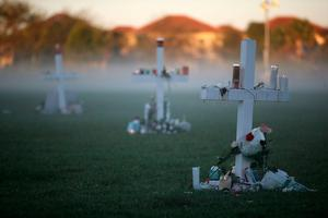 PARKLAND, FL - FEBRUARY 16: Candles that were placed on crosses still glow after last nights vigil for victims of the mass shooting at Marjory Stoneman Douglas High School, at Pine Trail Park, on February 16, 2018 in Parkland, Florida. Police arrested 19 year old former student Nikolas Cruz for killing 17 people at the high school.  (Photo by Mark Wilson/Getty Images)