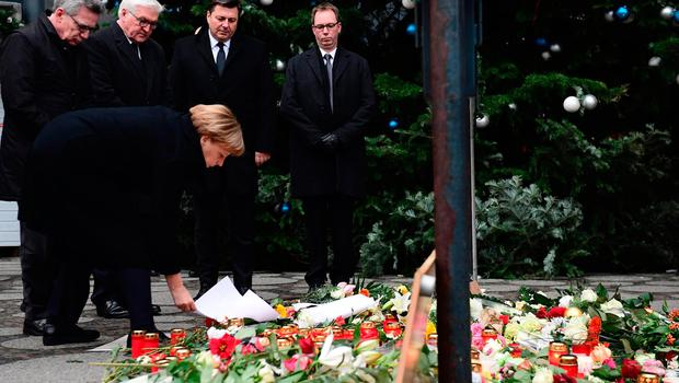 German Chancellor Angela Merkel (foreground), German Interior Minister Thomas de Maiziere (L) and German Foreign Minister Frank-Walter Steinmeier (2nd L) stand at a makeshift memorial for the victims of an attack on December 20, 2016 in front of the Kaiser-Wilhelm-Gedaechtniskirche (Kaiser Wilhelm Memorial Church) in Berlin, where a truck crashed into a Christmas market. Twelve people were killed and almost 50 wounded, 18 seriously, when the lorry tore through the crowd on December 19, 2016, smashing wooden stalls and crushing victims, in scenes reminiscent of July's deadly attack in the French Riviera city of Nice. / AFP PHOTO / Tobias SCHWARZTOBIAS SCHWARZ/AFP/Getty Images