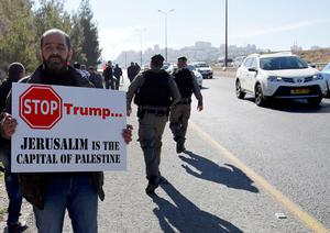 A Palestinian protester holds a placard during a demonstration against the construction of Jewish settlements in the occupied West Bank and against US President-elect Donald Trump, on January 20, 2017, near the settlement of Maale Adumim, east of Jerusalem. / AFP PHOTO / ABBAS MOMANIABBAS MOMANI/AFP/Getty Images