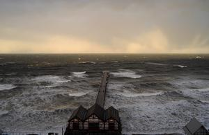SALTBURN, UNITED KINGDOM - DECEMBER 05: Waves begin to break against Saltburn pier during the storm surge on December 5, 2013 in Saltburn, United Kingdom. Strong winds and big tides are expected to cause coastal flooding along many of the east coast of England.  (Photo by Ian Forsyth/Getty Images)