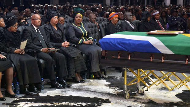 South African President Jacob Zuma sits between Winnie Madikizela-Mandela, left, Nelson Mandela's former wife, and Nelson Mandelas widow Graca Machel during the funeral service for former South African President Nelson Mandela in Qunu, South Africa, Sunday, December 15, 2013. (AP Photo/Odd Andersen, Pool)