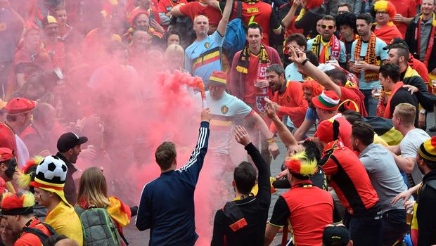 A Belgium's supporters waves a torch next to other supporters at the main square, La Grand Place, in Lille on July 1, 2016 ahead of the Euro 2016 football tournament quarter final match between Belgium and Wales. / AFP PHOTO / PHILIPPE HUGUENPHILIPPE HUGUEN/AFP/Getty Images
