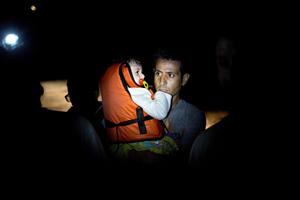 "A migrant holds his child as they arrive on the Greek island of Kos, after crossing a part of the Aegean Sea between Turkey and Greece, on August 11, 2015. The number of migrants and refugees arriving on Greece's shores has exploded this year, but the Mediterranean country provides virtually no reception facilities and leaves them wallowing in ""totally shameful"" conditions, a UN official said on August 7. AFP PHOTO / ANGELOS TZORTZINISANGELOS TZORTZINIS/AFP/Getty Images"