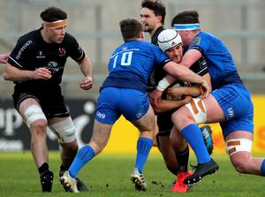 Ulster 'A' centre Ben Carson is wrapped up in a double tackle by Leinster 'A' pair David Hawkshaw and Joe McCarthy (INPHO/James Crombie)