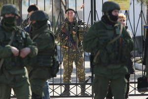An armed Ukrainian soldier stands inside the gate of a Ukrainian military base as unidentified heavily-armed soldiers stand outside in Crimea on March 3, 2014 in Perevalne, Ukraine
