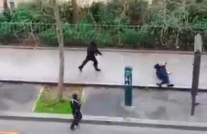 Masked gunman run towards a victim of their gun fire  outside the  French satirical newspaper Charlie Hebdo's office, in Paris, Wednesday, Jan. 7, 2015.  (AP Photo)