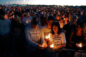 Jorge Zapata, Jr., center, a student at Marjory Stoneman Douglas High School, holds candles with his mother Lavinia Zapata, and father Jorge Zapata, Sr., during a candlelight vigil for the victims of the shooting at the school.
