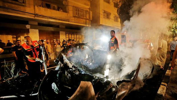 Smoke rises from a vehicle, destroyed by an Israeli strike, after Palestinian fire fighters put out the fire, in Gaza City, early Saturday, July 26, 2014. (AP Photo/Lefteris Pitarakis)
