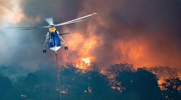A helicopter tackles a wildfire in East Gippsland, Victoria state, Australia. Credit: State Government of Victoria via AP