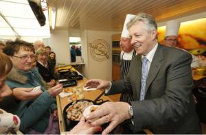 Press Eye - Belfast - Northern Ireland - 15th May 2012 - First day of the 2013 Balmoral Show in partnership with Ulster Bank at the new site, Balmoral Park.  First Minister Peter Robinson serves food to members of the public at the Ulster Pork and Bacon Forum at the beginning of the show. Picture by Kelvin Boyes / Press Eye