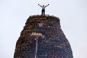 "Men stand on a bonfire under construction in the Ballymacash area of Lisburn, as building continues on huge loyalist bonfires, which are traditionally lit on the ""Eleventh night"" to usher in the Twelfth commemorations. PRESS ASSOCIATION Photo. Picture date: Sunday July 10, 2016. Authorities in Northern Ireland are cautiously optimistic the main fixture in the loyal order parading season can pass off peacefully, but have a major policing operation planned to deal with any unrest. See PA story ULSTER Twelfth. Photo credit should read: Brian Lawless/PA Wire"