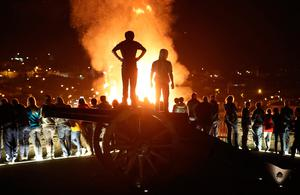 People watch a bonfire, from the top of a cannon on Derry city walls in the bogside area of Derry. Niall Carson/PA Wire