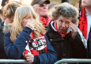 People react as they start to gather to pay their respects outside St George's Hall in Liverpool, north west England on April 27, 2016, in remembrance of the 96 Liverpool fans who died in the 1989 Hillsborough football stadium disaster. Thousands of sympathisers were expected to pay an emotional tribute to the Hillsborough disaster victims today after a landmark inquest found that 96 Liverpool football fans were unlawfully killed. / AFP PHOTO / PAUL ELLISPAUL ELLIS/AFP/Getty Images