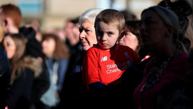 LIVERPOOL, ENGLAND - APRIL 27:  A young boy wearing a liverpool FC shirt joins thousands of people gathering outside Liverpool's Saint George's Hall to attend a vigil for the 96 victims of the Hillsborough tragedy on April 27, 2016 in Liverpool, England. The civic commemoration event marks the outcome of the fresh inquests into the 1989 Hillsborough disaster, in which 96 football supporters were crushed to death, and concluded yesterday with a verdict of unlawful killing. Relatives, Liverpool supporters and members of the public are taking part in the vigil at St George's Hall where a candle is lit for each of the 96 victims who lost their lives during a crush at the Hillsborough football ground in Sheffield, South Yorkshire in 1989..  (Photo by Christopher Furlong/Getty Images)