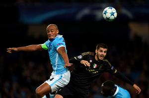 Manchester City's Belgian defender Vincent Kompany (L) jumps for a header with Juventus' forward from Spain Alvaro Morata during a UEFA Champions League group stage football match between Manchester City and Juventus at the Etihad stadium in Manchester, north-west England on September 15, 2015.       AFP PHOTO / PAUL ELLISPAUL ELLIS/AFP/Getty Images