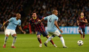 Barcelona's Lionel Messi knocks the ball past Manchester City's Vincent Kompany during the UEFA Champions League, Round of 16 match at the Etihad Stadium, Manchester. PRESS ASSOCIATION Photo. Picture date: Tuesday February 18, 2014. See PA story SOCCER Man City. Photo credit should read: Martin Rickett/PA Wire