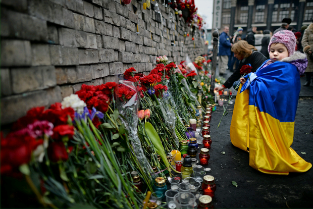 A young girl lays flowers left for anti-government demonstrators killed in clashes with police on February 22, 2014 in Kiev, Ukraine. Photo by Jeff J Mitchell/Getty Images