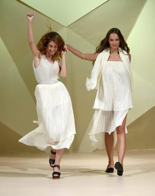 DUBAI, UNITED ARAB EMIRATES - OCTOBER 04:  Fashion designer Timi Hayek (L) on the runway after her show at the Starch Foundation Designers show during Fashion Forward at Madinat Jumeirah on October 4, 2014 in Dubai, United Arab Emirates.  (Photo by Ian Gavan/Getty Images for Fashion Forward)