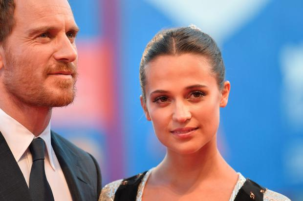 "British actor Michael Fassbender and Swedish actress Alicia Vikander, pose on the red carpet before the premiere of the movie ""The Light Between Oceans"" presented in competition at the 73rd Venice Film Festival on September 1, 2016 at Venice Lido. / AFP PHOTO / TIZIANA FABITIZIANA FABI/AFP/Getty Images"