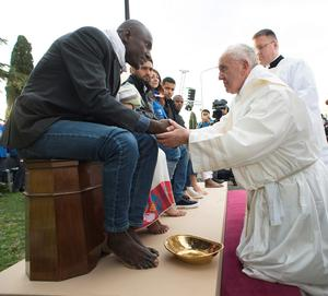 Pope Francis shakes hands with a man during the foot-washing ritual at the Castelnuovo di Porto refugees center near Rome on March 24, 2016. AFP/Getty Images