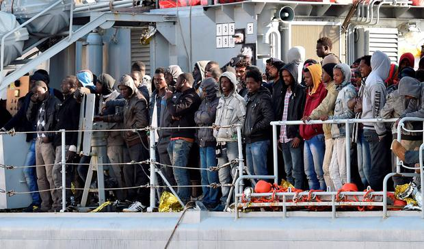 """Migrants stand on the deck of the Italian Navy ship """"Driade"""" prior to being disembarked in Messina's port, Sicily, Italy. (AP Photo/Carmelo Imbesi)"""