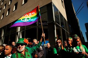 NEW YORK, NY - MARCH 17:  A man holds up a Gay Pride flag at the annual St. Patrick's Day parade, one of the largest and oldest in the world on March 17, 2016 in New York City. Now that a ban on openly gay groups has been dropped, New York Mayor Bill de Blasio is attending the parade for the first time since he became mayor in 2014. The parade goes up Fifth Avenue ending at East 79th Street and will draw an estimated 2 million spectators along its 35-block stretch.  (Photo by Spencer Platt/Getty Images)