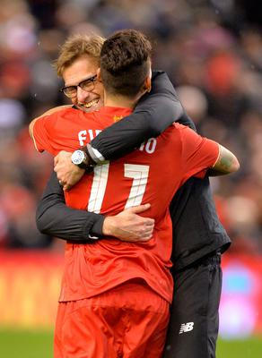 Liverpool's German manager Jurgen Klopp (L) embraces Liverpool's Brazilian midfielder Roberto Firmino after winning the penalty shoot-out in the English League Cup semi-final second leg football match between Liverpool and Stoke City at Anfield in Liverpool, north west England, on January 26, 2016. Liverpool won the two legged semi-final 6-5 on penalties, after a 1-0 Stoke victory in 90 minutes meant the tie finished 1-1 after extra time. / AFP / Paul ELLIS / RESTRICTED TO EDITORIAL USE. No use with unauthorized audio, video, data, fixture lists, club/league logos or 'live' services. Online in-match use limited to 75 images, no video emulation. No use in betting, games or single club/league/player publications.  / PAUL ELLIS/AFP/Getty Images