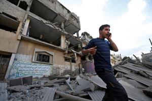 A Palestinian talks on a mobile phone as he walks on the rubble of a damaged house following an overnight Israeli missile strike in Gaza City, Tuesday, July 15, 2014 (AP Photo/Lefteris Pitarakis)