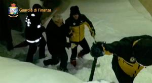 This image grab made from a video handout released by the Guardia di Finanza on January 19, 2017 shows a man being escorted by Alpine policemen (R) and a fireman (L) outside the Hotel Rigopiano, near the village of Farinfola, on the eastern lower slopes of the Gran Sasso mountain.  / AFP PHOTO / Guardia di Finanza press office /