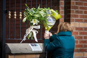 A woman leaves flowers at the gates of Connolly House, Andersonstown, Belfast after the death of Northern Ireland's former deputy first minister and ex-IRA commander Martin McGuinness aged 66. Liam McBurney/PA Wire