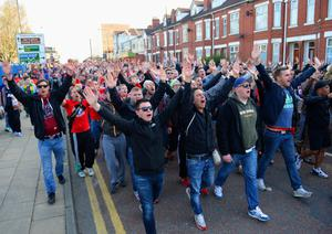 MANCHESTER, ENGLAND - APRIL 01:  Football fans sing as they make their way to the ground ahead of the UEFA Champions League Quarter Final first leg match between Manchester United and FC Bayern Muenchen at Old Trafford on April 1, 2014 in Manchester, England.  (Photo by Michael Regan/Bongarts/Getty Images)