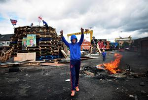 BELFAST, NORTHERN IRELAND - JULY 11: Loyalists make final preparations to their bonfire on the Newtownards road on July 11, 2016 in Belfast, Northern Ireland. The lighting of the bonfires at midnight on the eleventh night marks the start of the annual twelfth of July celebrations within the protestant community. The Orange marches and demonstrations celebrate the Battle of the Boyne in 1690 when the Protestant King William of Orange defeated the Catholic King James II on the banks of the river Boyne. (Photo by Charles McQuillan/Getty Images)