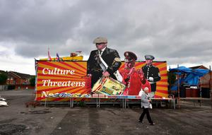 BELFAST, NORTHERN IRELAND - JULY 11: A woman walks past tables stacked with sweets, fizzy drinks and crisps as Loyalists make final preparations to their bonfire on the Newtownards road on July 11, 2016 in Belfast, Northern Ireland. The lighting of the bonfires at midnight on the eleventh night marks the start of the annual twelfth of July celebrations within the protestant community. The Orange marches and demonstrations celebrate the Battle of the Boyne in 1690 when the Protestant King William of Orange defeated the Catholic King James II on the banks of the river Boyne. (Photo by Charles McQuillan/Getty Images)