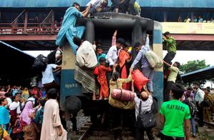 Bangladeshi Muslims try to board an overcrowded train to head home for Eid al-Fitr celebrations as others wait at a railway station in Dhaka, Bangladesh, Thursday, Aug. 8, 2013. The mass exodus out of the capital and other major cities in the country is underway as millions are heading back to their home towns to celebrate Eid al-Fitr holiday which marks the end of the holy fasting month of Ramadan. (AP Photo/A.M. Ahad)