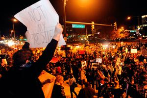 A demonstrator holds up a sign as others protest the election of President elect Donald Trump in Denver, Colorado on November 10, 2016. / AFP PHOTO / Jason ConnollyJASON CONNOLLY/AFP/Getty Images