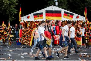 BERLIN, GERMANY - JUNE 21: Football fans passing a souvenier stand as fans celebrate the 2016 UEFA European Championship match between Germany and Northern Ireland 1:0 at a public viewing area on a large outdoor screen at Brandenburg Gate on June 21, 2016 in Berlin, Germany. (Photo by Carsten Koall/Bongarts/Getty Images)